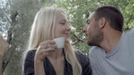 Romantic couple of happy man and woman in love, smile and kiss during italian breakfast in natural rural scenic outdoor during summer sunny day morning in tuscany - slow-motion HD video footage video