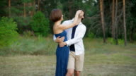 Romantic couple of young people are embracing a clearing in the summer forest video