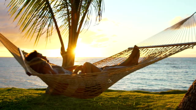 Romantic couple relaxing in tropical hammock at sunset. Summer Luxury Vacation. video