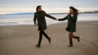 Romantic couple running and jumping on the beach together and having a date along the seashore. Husband dressed in coat is looking at his wife with love and tenderness. Young woman in black coat video