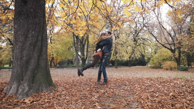 Romantic couple running towards each other and spinning out of joy in autumn park. video