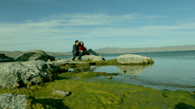 Romantic couple sitting on the stone on the beach. video