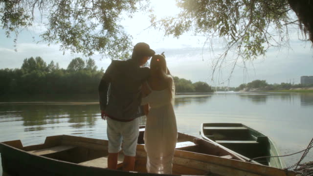 Romantic couple talking in old boat on sunset video