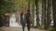 Romantic Couple Walk On Fall Street In City In Slow Motion video