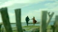 Romantic couple walking and having fun on the beach. video
