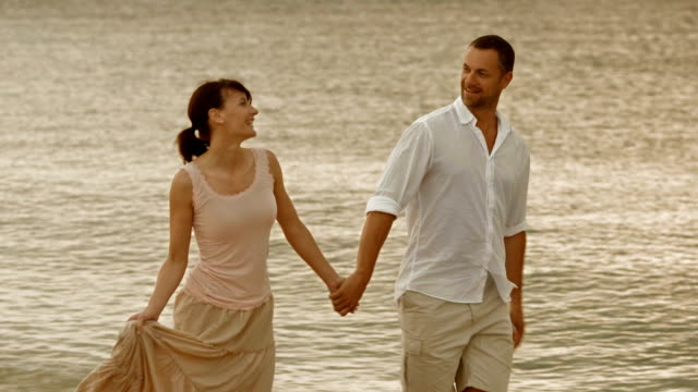 Romantic couple walking by the shore holding hands video