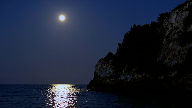 Romantic fullmoon about the Mediterranean Sea at night on Cala Romantica on Spanish Balearic island of Majorca / Spain video
