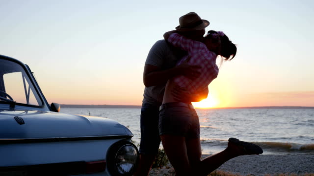 Romantic kiss on nature near water, summer rest of young couple on shore river on sunset, meet of happy Lovers video