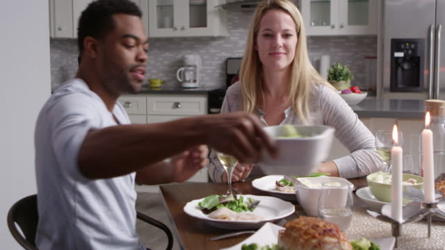 Romantic mixed race couple making a toast at meal in kitchen, shot on R3D video