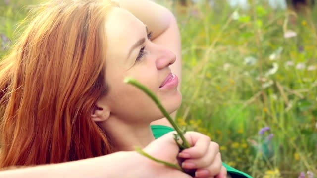 Romantic red-haired young woman in green smiles dress and lays down on a flower meadow. relaxing on grass video
