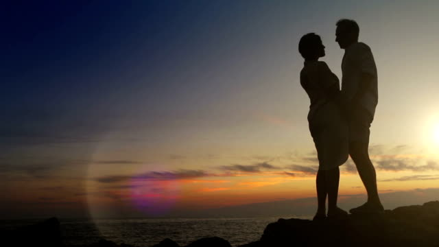 Romantic scene at sunset: couple kissing on their honeymoon video