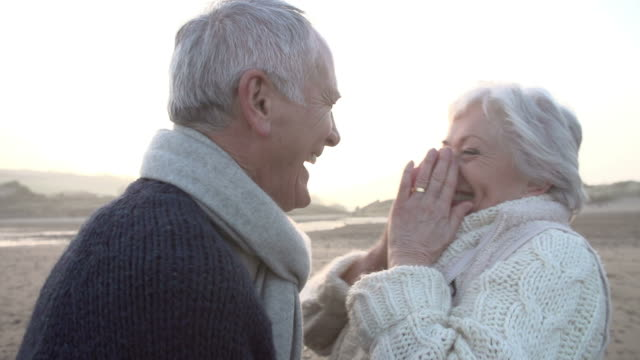 Romantic Senior Couple Embracing On Winter Beach In Slow Motion video