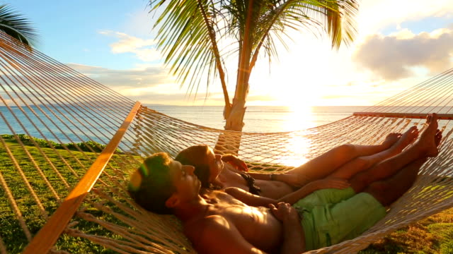 Romantic young couple relaxing in tropical hammock at sunset video