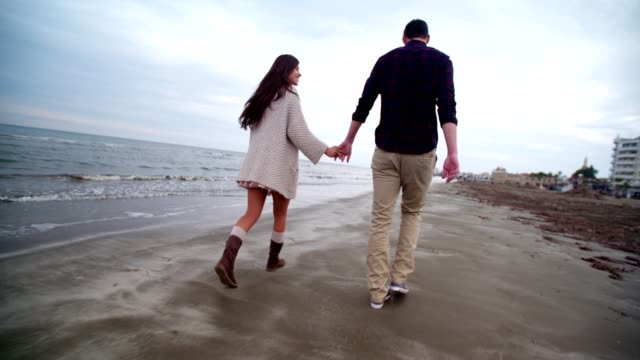 Romantic young couple walking on the beach and holding hands video