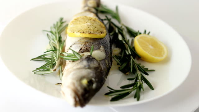 Rotating baked fish seabass on a white plate video