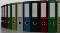Rotating color office binders, shallow focus. FullHD seamless loopable animation video