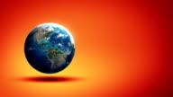 Rotating Earth on red/orange studio background video