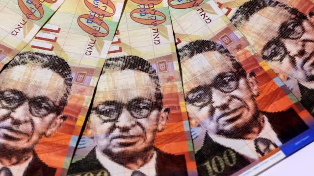 Rotating israeli money bills of one hundred shekel - top view video