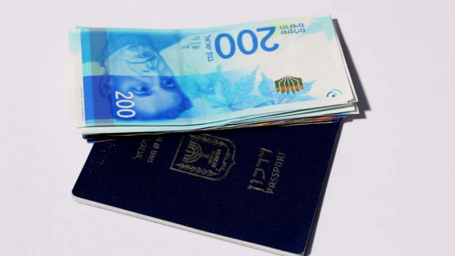 Rotating israeli money bills of two hundred shekel and israeli passport  - top view video