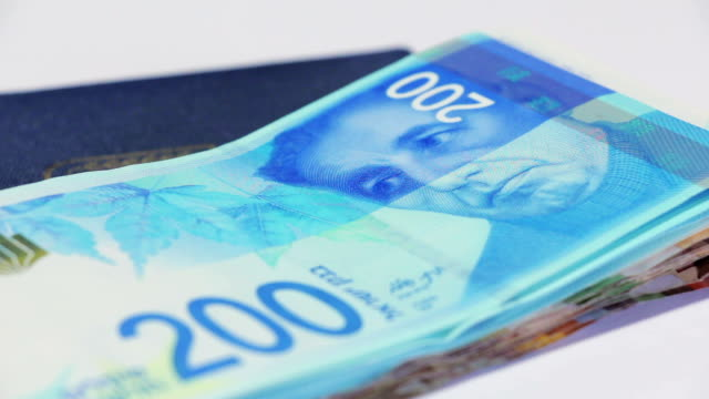 Rotating israeli money bills of two hundred shekel and israeli passport video