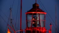 Rotating lighthouse at dusk in harbor video