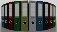 Rotating multicolored office binders, shallow focus. FullHD seamless loopable animation video