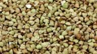 Rotating raw buckwheat, dry uncooked seeds closeup video