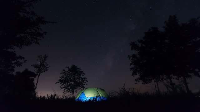 Rotating stars above tent at night. Time lapse video