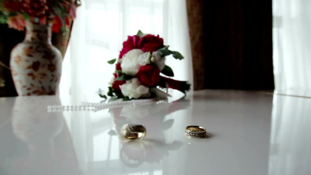 Rotating wedding rings near bouquet on the piano video