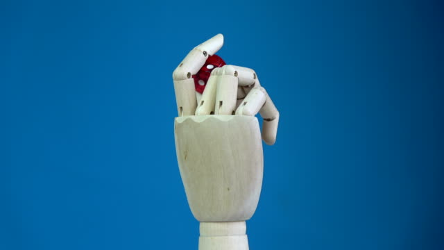 Rotating wooden manikin hand with red lucky dice video