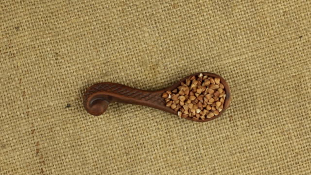 Rotation of a clay spoon with buckwheat grain, background for design. video