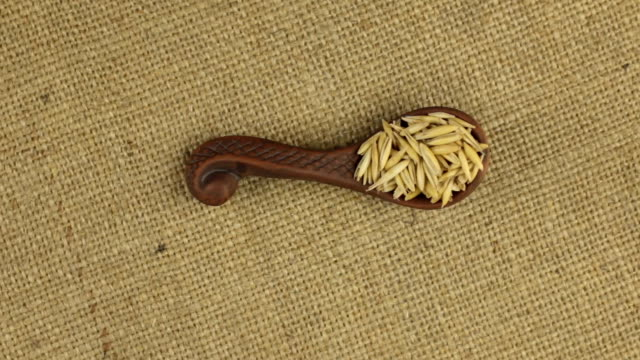 Rotation of a clay spoon with oat grain, background for design. video