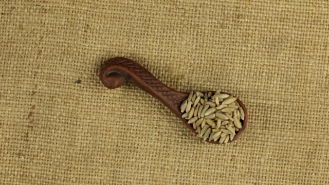 Rotation of a clay spoon with rye grain, background texture for design. video