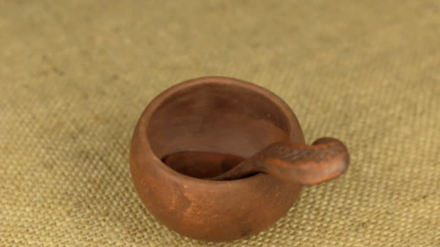Rotation of clay pot and spoon on burlap. video