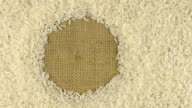 Rotation of the rice grains lying on sackcloth with space for your text video