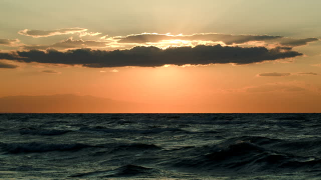 Rough sea and evening sun hidden with cloud video