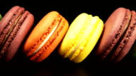Row of a colorful macaroons is on the black background video