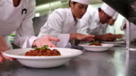 Row of chefs garnishing spaghetti dishes video