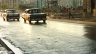 Row of classic cars driving in golden hour sunset in Havana video