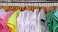 Row of colorful shirts on hangers in a clothing store close-up video
