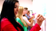 Row of focused students writing on whiteboard in classroom video
