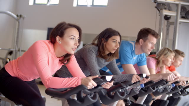 A row of people on exercise bikes in a spinning class at gym video