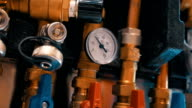 A row of red and blue water valves and pressure gauges regulating the water video