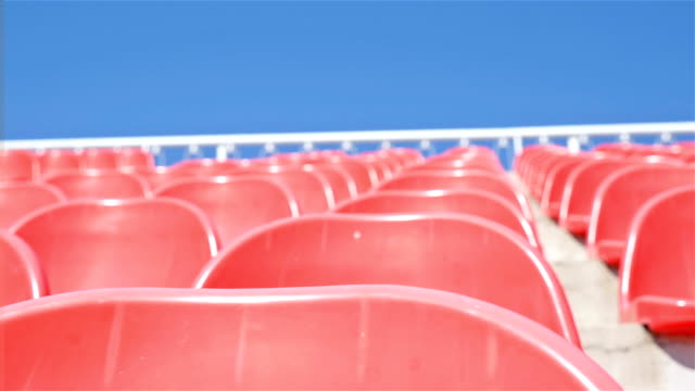 Rows of red plastic seats on stadium , dolly video