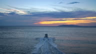 AERIAL Rubber boat riding on sea at sunset video