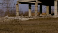 Ruined buildings abroad from barbed wire video