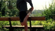 Runner stretching his leg in beautiful nature video
