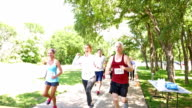 Runners in marathon or 5k charity race are jogging past toward finish line video