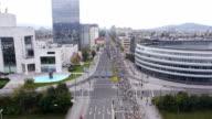 AERIAL: Runners on city streets running marathon over the highway bridge video