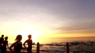 Runners running on promenade by the sea in sunset video